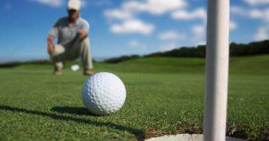 golf ball on the green near the hole