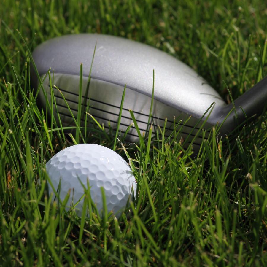 hybrid golf club getting ready to hit a golf ball